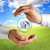 hands enclosing a house in a bubble above grass field and blue sky background